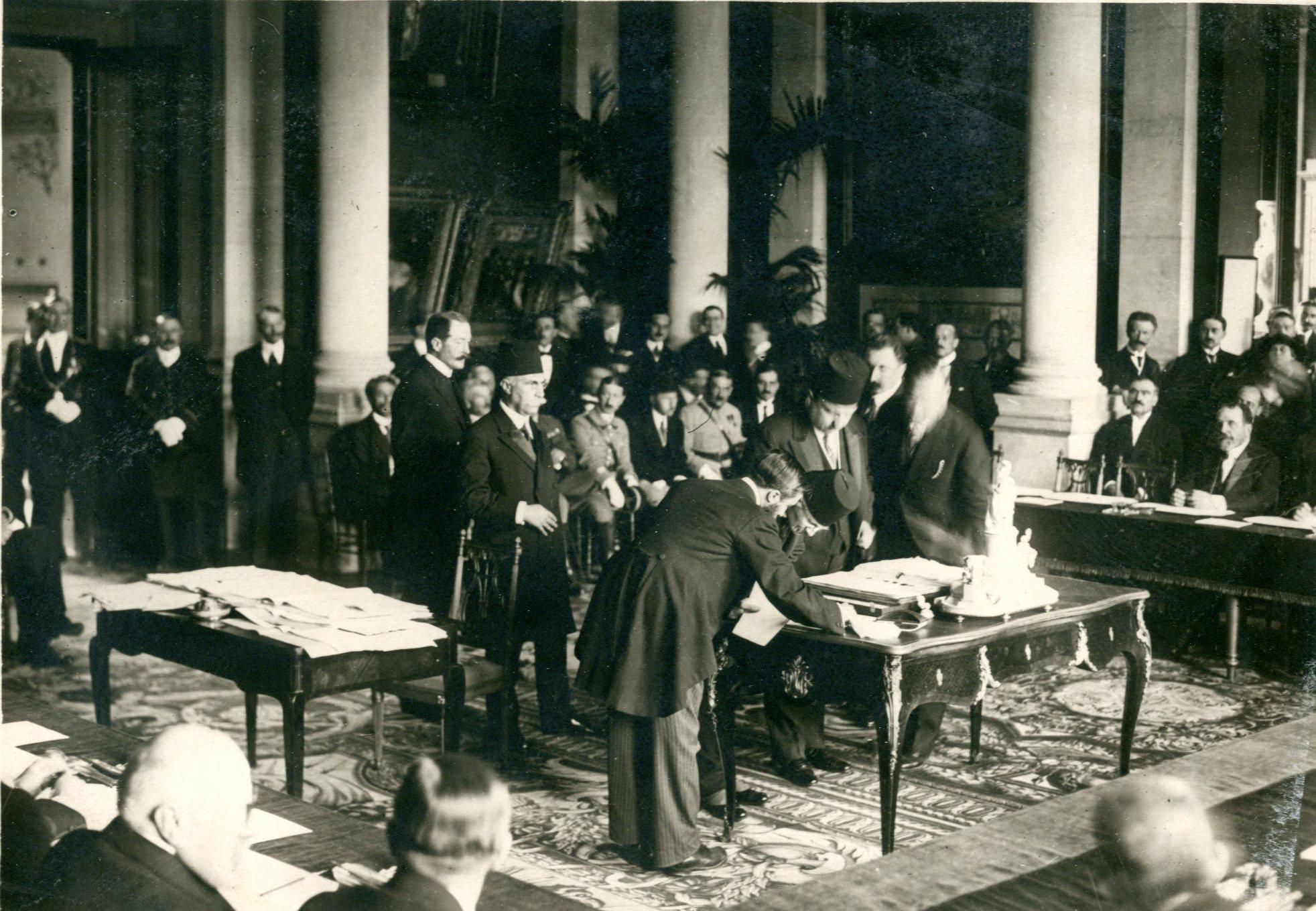 Sevr Antlaşmasını imzalamak ile görevlendirilen Reşad Halis ve Rıza Tevfik Beyler ile Hâdi Paşa, sırayla antlaşma menünü imza ederlerken.